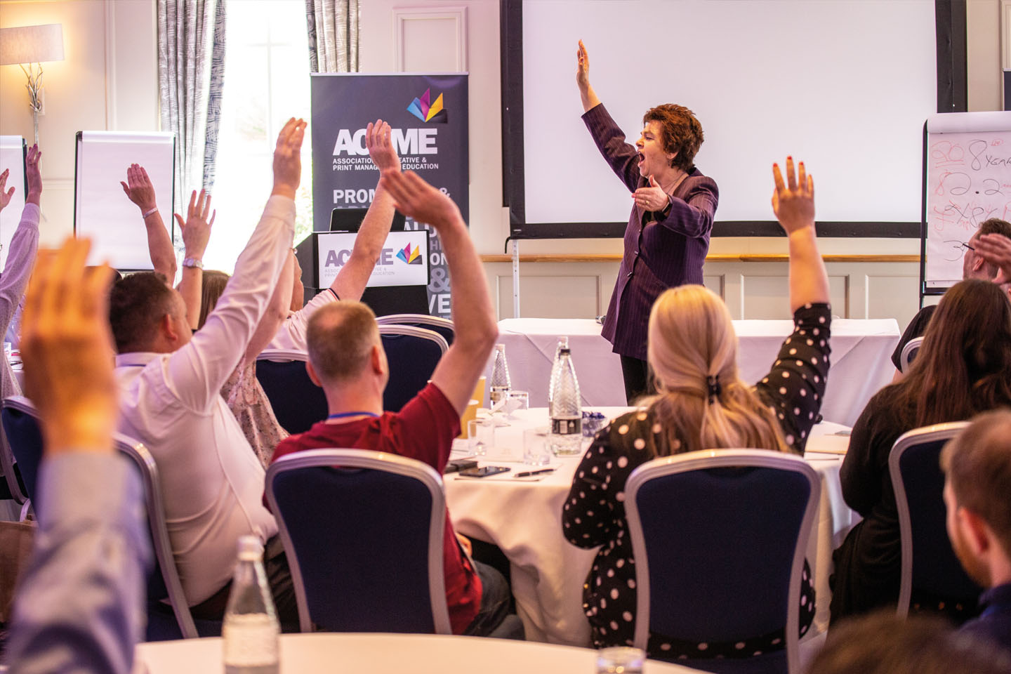 Kate asking 'Who feels part of the ACPME family?' at conference